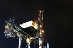 Port crane for shipping containers. Dutch Harbor, Unalaska, Alaska, USA - August 14th, 2017: Night view of a port crane for shipping containers operated by Royalty Free Stock Images