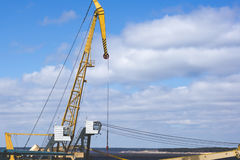 Port crane with yellow arrow against the blue sky and clouds. Ri Royalty Free Stock Photos