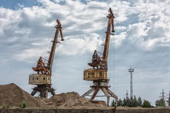 Port cranes against the background of clouds. Rusty port cranes stand against the background of clouds and blue sky Royalty Free Stock Image