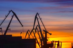 Port cranes on the background of sunset. royalty free stock photography