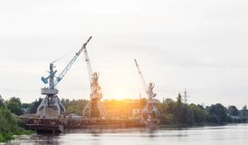 Port cranes with a bucket on the river bank, extraction of river sand, the sun stock image