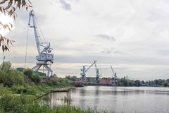 Port cranes with a bucket on the river bank, extraction of river sand stock photo