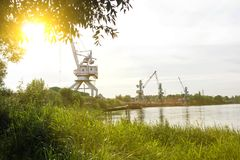 Port cranes with a bucket on the river bank, extraction of river sand, the sun royalty free stock photo