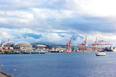 Port cranes and buildings under blue cloudy sky in Seattle downtown. Royalty Free Stock Images