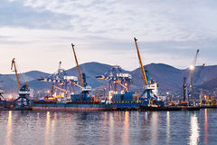 Port cranes in dock by sea at twilight Royalty Free Stock Photo