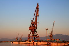 Port cranes in the empty morning harbor of Rijeka, Croatia. Port cranes in the empty harbor in the morning sunrise with Ucka mountain, Istria, in the background Stock Photos