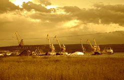 Port cranes evening lake scenery. Scrap metal heaps,port machinery on Varna lake beautiful twilight scenery,Bulgaria Stock Photography
