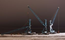 Port cranes in expectation of arrival of a vessel. Dudinka, Russian Federation Royalty Free Stock Image