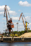 Port cranes on the fortified banks of the Volga River. Port cranes unload sand in the district of the Bor glass plant Stock Images