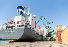 Port cranes loading container ship with cargo Royalty Free Stock Photo
