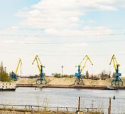 Port cranes on the river bank stock image