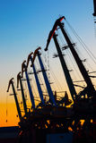 Port cranes at sunset Stock Photos