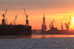 Port cranes at sunset stock images