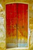 PORT D ANDRATX, SPANIEN - AUGUSTI 18 2017: Stäng sig upp av en liten gammal brun dörr i en skadad vägg, i stad för port D Andratx Royaltyfri Fotografi