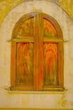 PORT D ANDRATX, SPANIEN - AUGUSTI 18 2017: Stäng sig upp av litet gammalt brunt fönster i en skadad vägg, i stad för port D Andra Arkivfoton