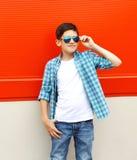 Port de garçon de bel enfant lunettes de soleil et chemise au-dessus du rouge Photographie stock libre de droits