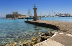 Port de Rhodes Mandraki avec le château et les statues symboliques de cerfs communs, Grèce Photographie stock libre de droits
