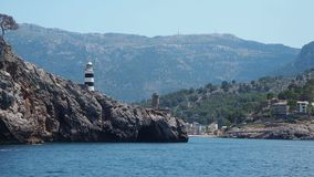Port de Soller, Mallorca, Spain. The lighthouse and the rocks around the village from the boat. Summer time stock video