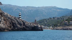 Port de Soller, Mallorca, Spain. The lighthouse and the rocks around the village from the boat. Summer time stock footage