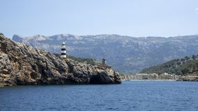 Port de Soller, Mallorca, Spain. The lighthouse and the rocks around the village from the boat royalty free stock photography