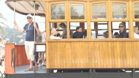 Old wooden vintage tram arrives in Port de Soller with tourists. PORT DE SOLLER, MALLORCA, SPAIN - MAY 10, 2018: Old wooden vintage tram arrives in Port de stock footage