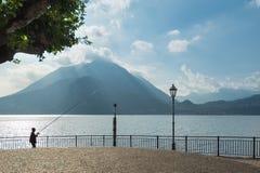 Port de Varenna au lac Como avec le pêcheur dans le contre-jour Photos libres de droits