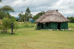 Thatched Roof. PORT DENARAU, FIJI-NOVEMBER 27,2016: Tropical landscape, village hut with thatch roof and storm clouds in Port Denarau, Fiji Stock Photography