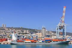 Port dock with container ship and Various brands and colors of shipping containers stacked in a holding platform Stock Image