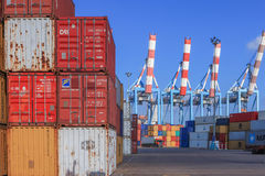 Port dock with container ship and Various brands and colors of shipping containers stacked in a holding platform Royalty Free Stock Photography