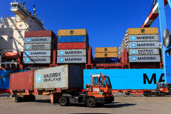 Port dock with container ship and Various brands and colors of shipping containers stacked in a holding platform Royalty Free Stock Images