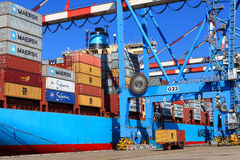 Port dock with container ship and Various brands and colors of shipping containers stacked in a holding platform Stock Photo