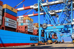 Port dock with container ship and Various brands and colors of shipping containers stacked in a holding platform Stock Images