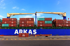 Port dock with container ship and Various brands and colors of shipping containers stacked in a holding platform Royalty Free Stock Photo