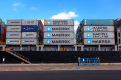 Port dock with container ship and Various brands and colors of shipping containers stacked in a holding platform Royalty Free Stock Photos