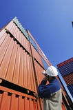 Port and dock worker with cargo containers. Port and dock worker talking in phone with stacks of cargo-containers in the background Royalty Free Stock Photo