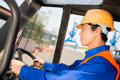 Port docker. Closeup image of a port docker in uniform driving a machine on the foreground Royalty Free Stock Photos