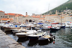 The port of Dubrovnik. DUBROVNIK, CROATIA - September 5, 2015: Boats anchored in the port of the old town of Dubrovnik. Only roofs are seen behind the town walls Royalty Free Stock Photos