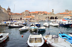 The port of Dubrovnik. DUBROVNIK, CROATIA - September 5, 2015: Boats anchored in the port of the old town of Dubrovnik. Only roofs are seen behind the town walls Royalty Free Stock Image