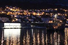 Port of Dubrovnik. Sailfish. Sailboat entering the port of Dubrovnik at night. Glowing in the background at home stock images
