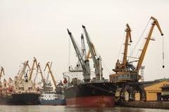 Port eller kommersiell hamn med lastfartyg och cran arkivfoto