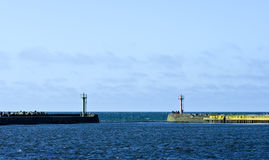 Port entrance beacons. Two beacons at the end of two jetties, clear horizon Stock Photos