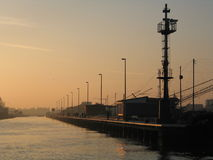 Port entrance. Rimini's port entrance at sunset with fishermen huts on the pier Royalty Free Stock Image
