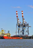 Port facilities with cranes and freight ship Stock Image