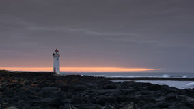 Port fairy lighthouse at sunrise with rocks. Light house situated on the rocky shore of Port fairy. Taken at sunrise with a cloudy sky Royalty Free Stock Photo