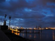 Port of Felixstowe at night with cranes and container ships. Lit up on a calm sea against a cloudy sky taken from Shotley Point, Suffolk, UK Royalty Free Stock Images