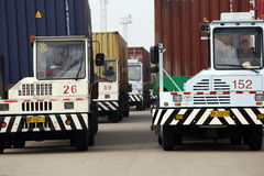 Port forwarding. Trailers uploading container at busy shipping port Stock Photos