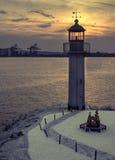 Port, fyr, solnedgång och två älskvärda fåglar Royaltyfria Bilder