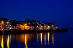 Port of Galway at night. With lights from the buildings reflecting off the water stock photo