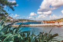 Ships in Skiathos harbor. The port on the Greek island of Skiathos with aloe vera in the foreground, September 2018 royalty free stock photography