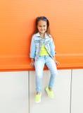Port heureux d'enfant de petite fille lunettes de soleil et vêtements de jeans Photos libres de droits
